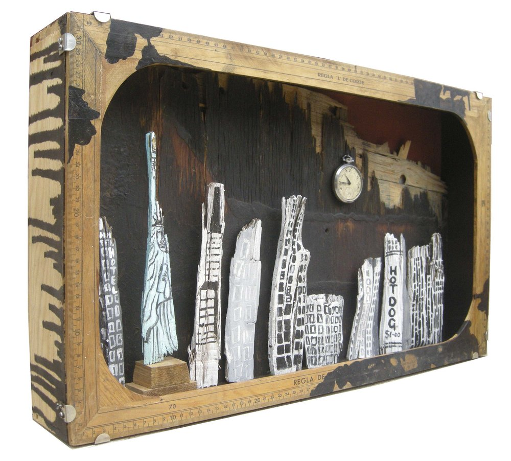 "911  Found Objects, wood, Pen & Ink, Asphalt  | W: 62 H: 37 D: 9.5 cm   ""Nine Eleven""  The wood-chips I used were found in Central Park looking at the NYC skyline, recognising the image of the burning Twin Towers was a lasting memory in our collective consciousness.  This assemblage was shortlisted for the  National Open Art Competition  2014"