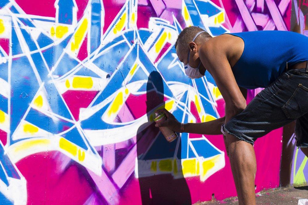 Lavie Raven graffiti artist at work in Toi Pōneke's car park