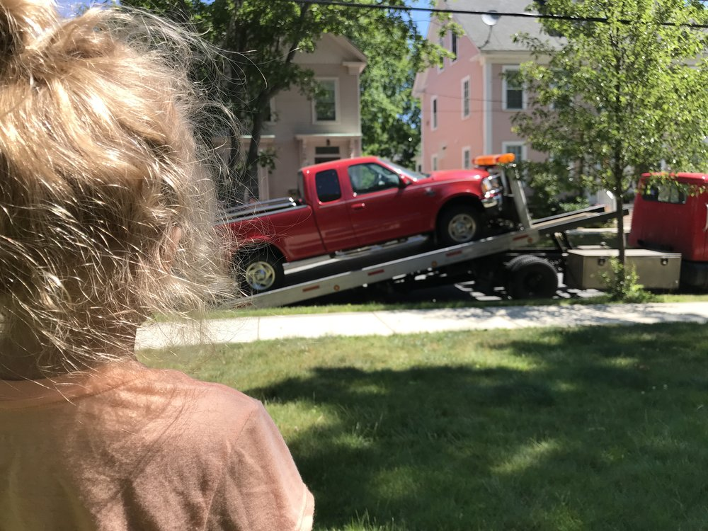 My daughter watching as the truck is prepared for the tow.
