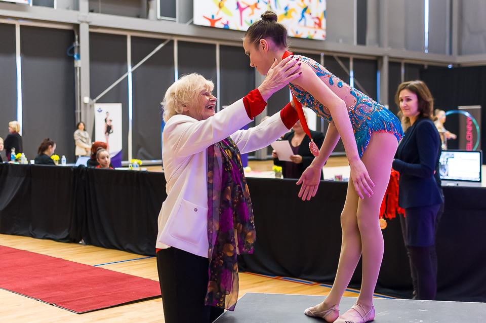 Mrs. Koop presenting an award to gymnast