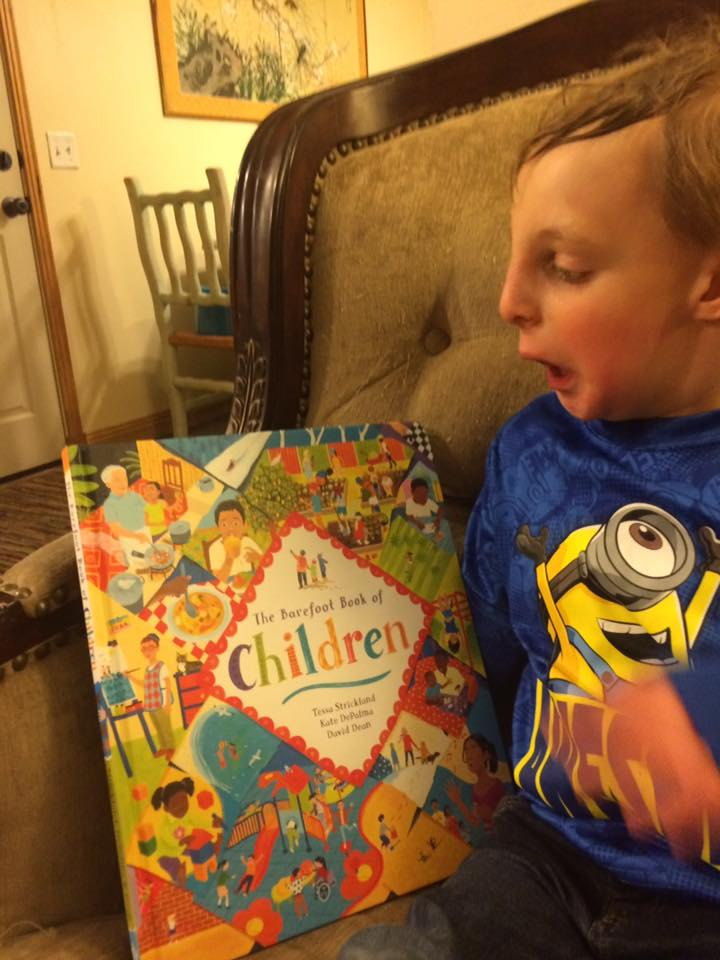 Atticus looking at The Barefoot Book of Children, which represents all children, including those with special needs.