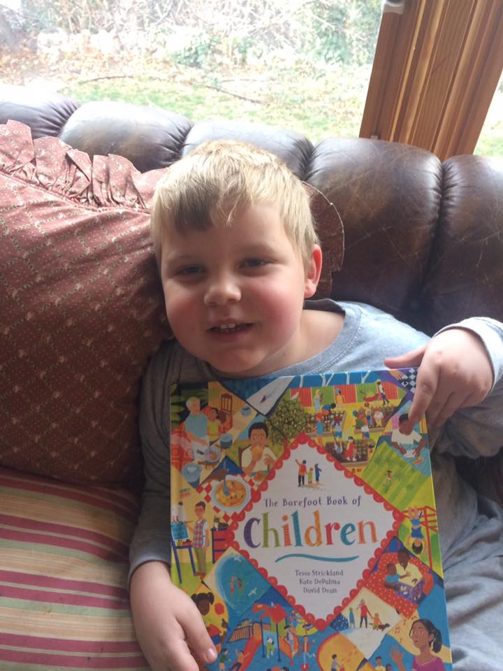 Damien holding The Barefoot Book of Children, the most diverse and inclusive work of children's literature I've ever read.