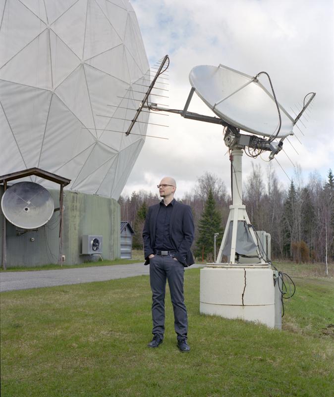 Joni Tammi standing in front of the Metsähovi radio telescope.