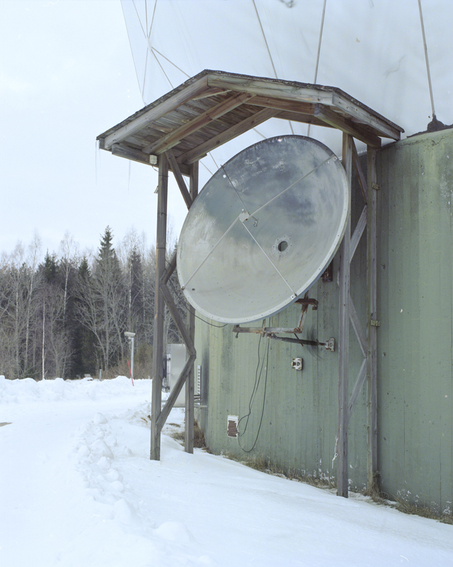 An old satellite dish situated on the side of the observatory in winter.