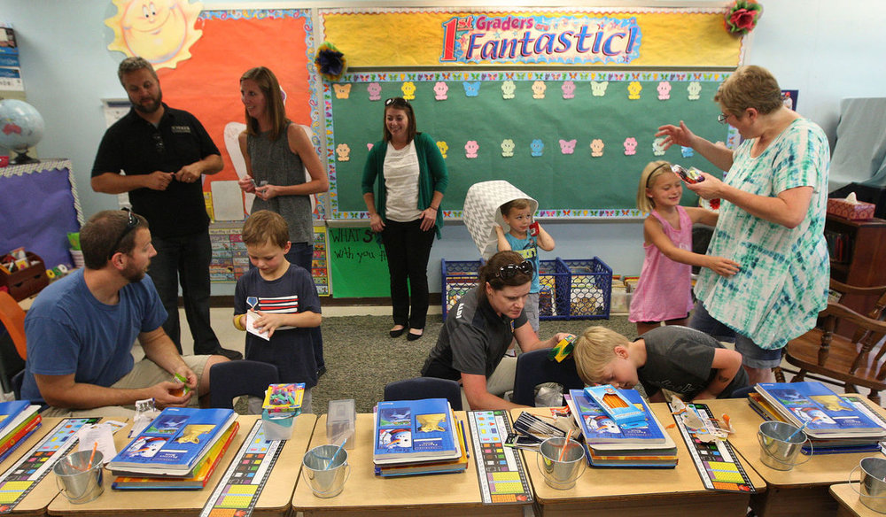 First grade teacher Jane De Freitas, standing far right, greets students and parents in her classroom during 'Meet the Teacher' night at Sangamon Valley East Elementary School on Monday.