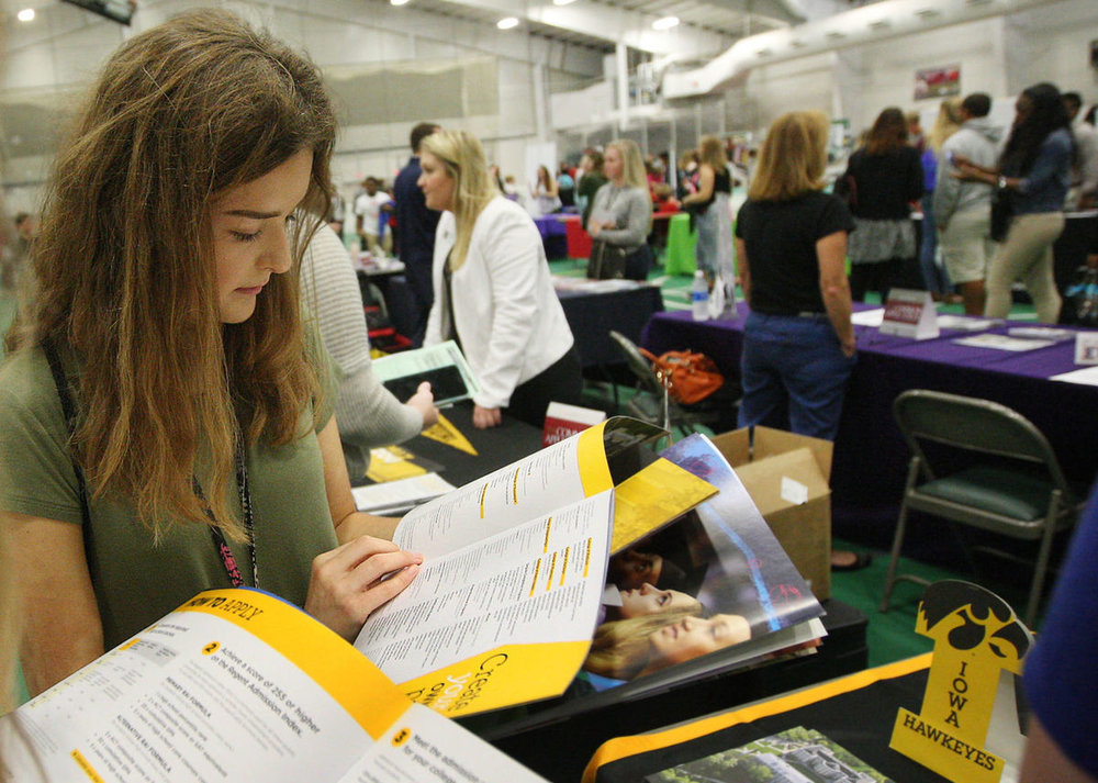 Sangamon Valley High School student Mackenzie Kokal looks over a pamphlet at the Iowa University table during the Decatur Area College and Career Fair at the Decatur Indoor Sports Center Tuesday morning.