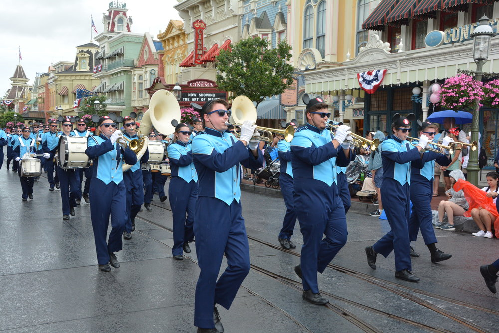 "The Marching Storm lead a parade down Main Street USA playing ""You're a Grand Old Flag"""