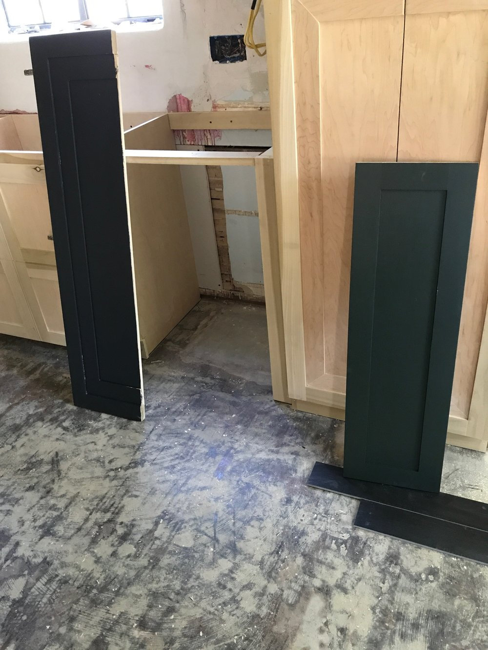 - Cindy and I went back and forth between black paint and dark green paint. We used some of the trial cabinet doors to test out colors.*also, notice the difference between a regular shaker (on the right) and the