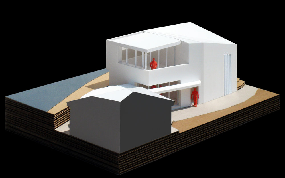 A model of the studio with a portion of the existing house in the foreground.