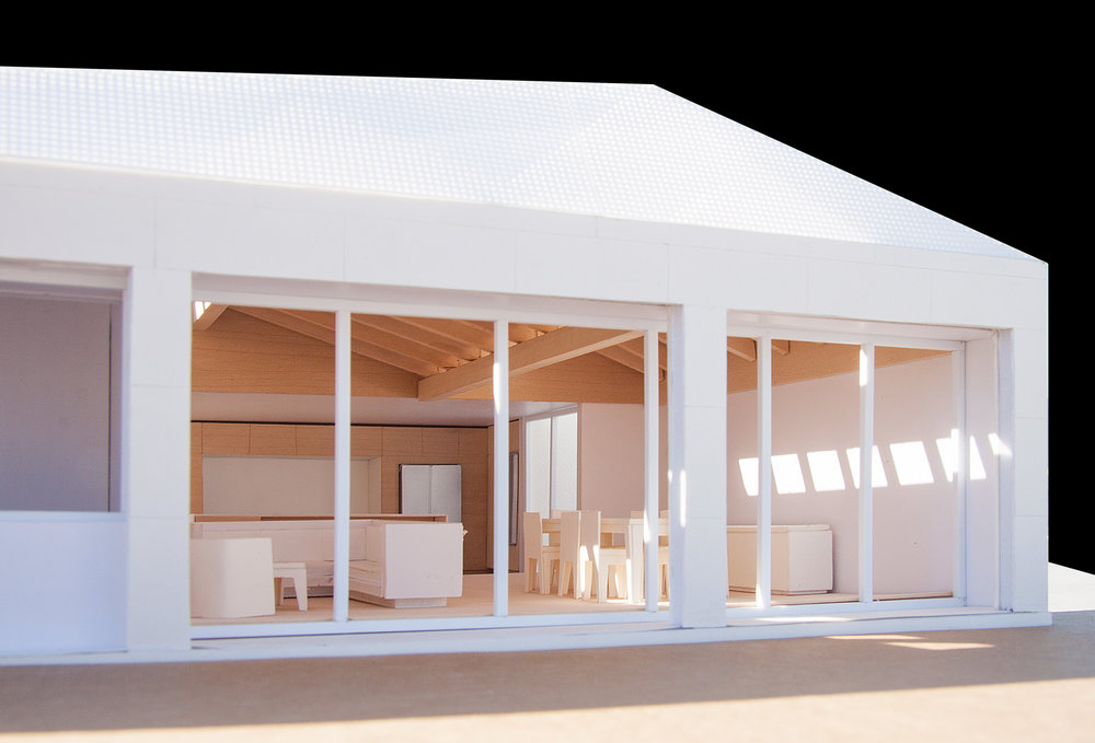 Photograph of model showing the skylights and wood clad vaulted ceiling with exposed beams.