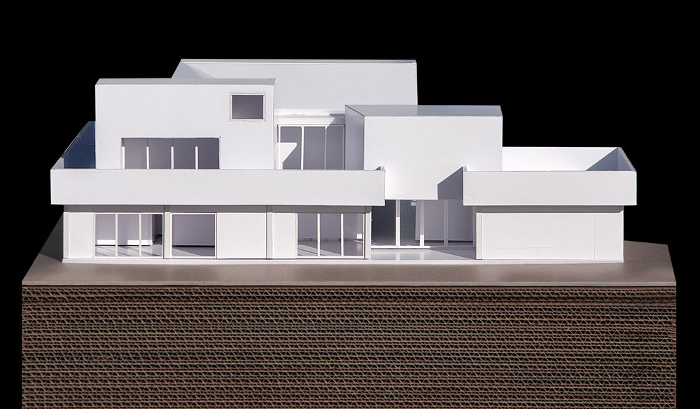 View of the model showing the front facade that faces the street with the recessed entrance and three bedroom volumes above.