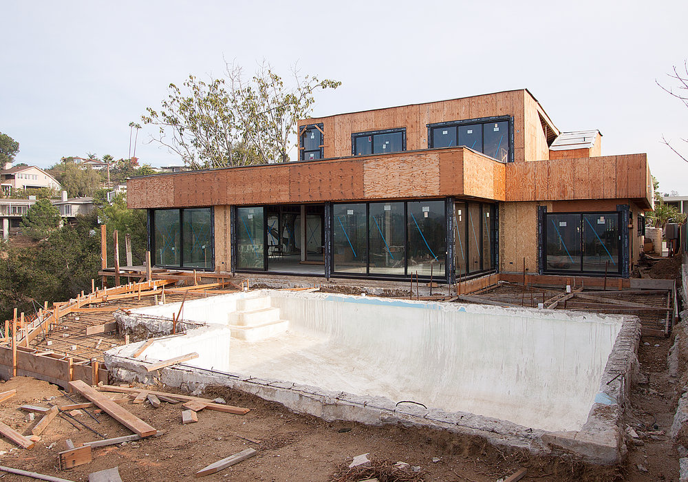 Construction photo showing the rear facade that faces the pool and the view beyond.