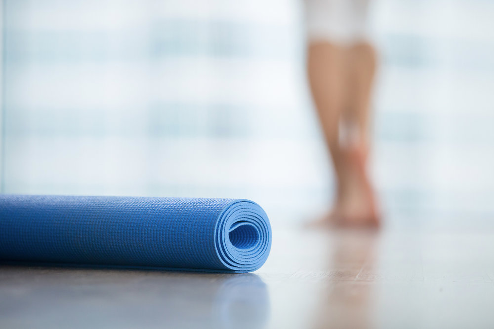 A yoga mat with a person in the background blurred out.