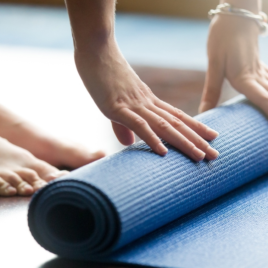 A person bends over reaching down to their pilates mat.