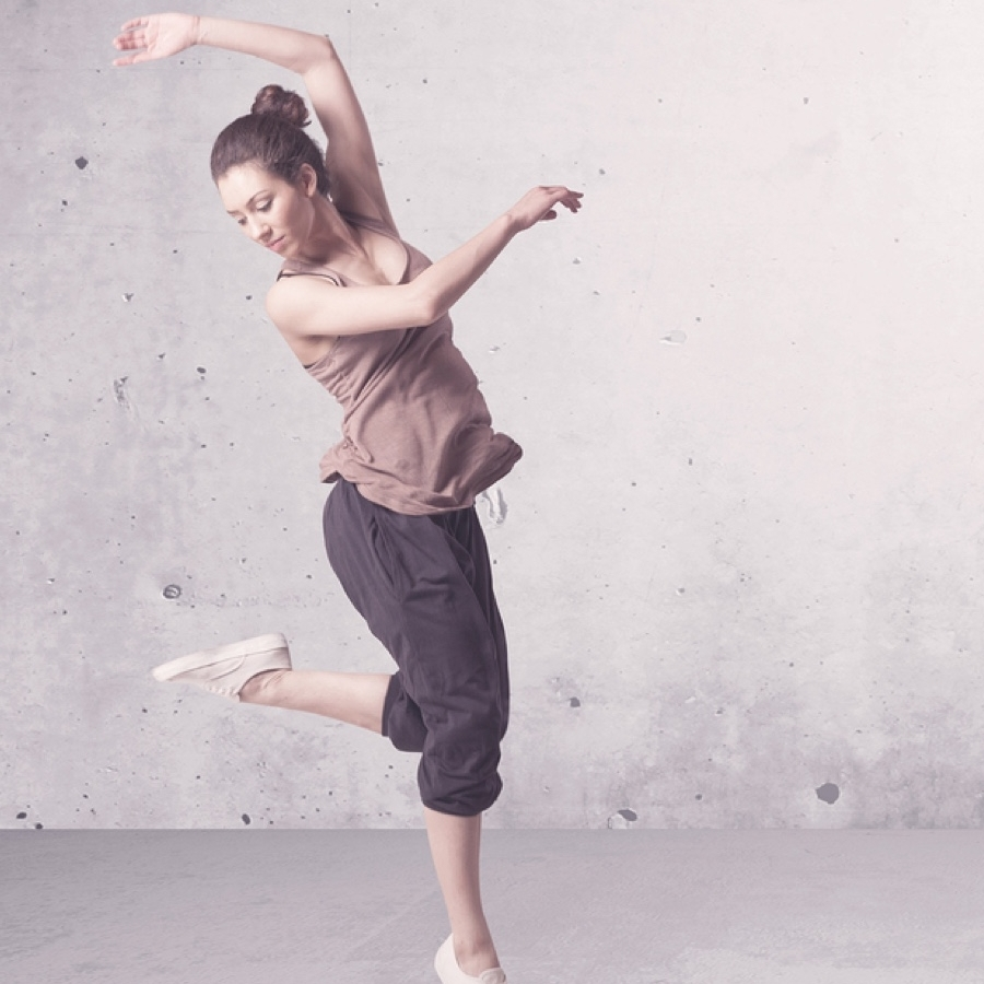 A dancer jumping in the air and twirling contently.