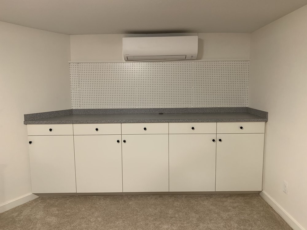 Wall to wall cabinets, countertop and peg board