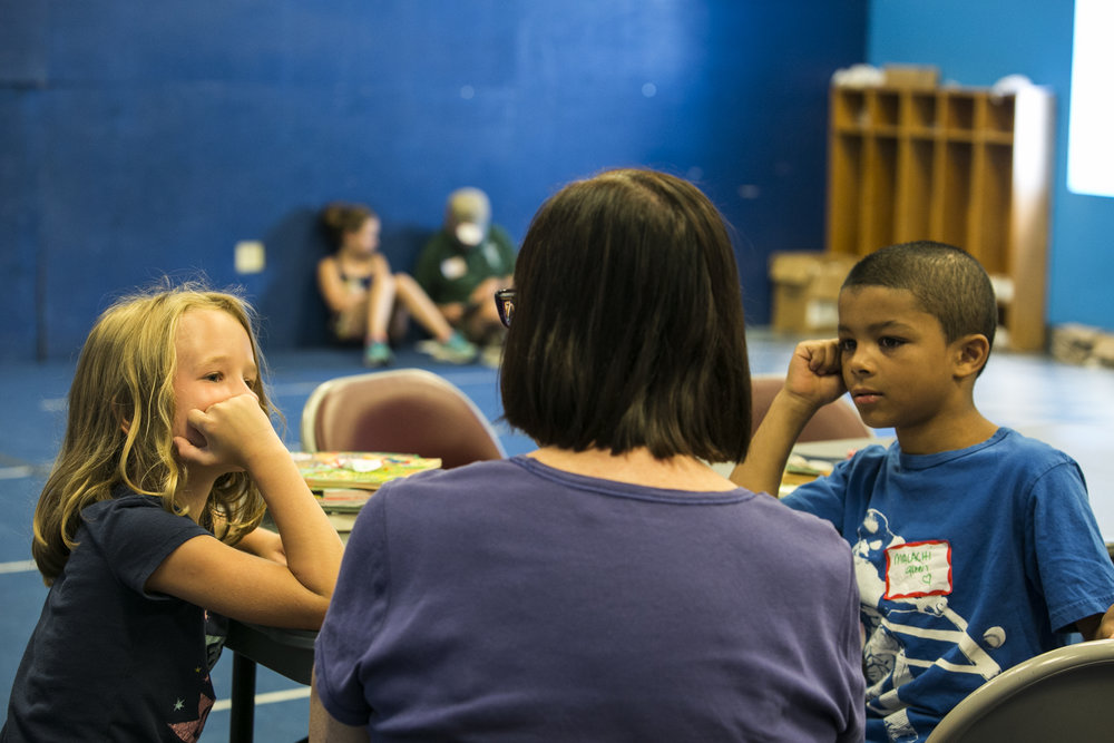 Brianne Burdick and Malachi Easley listen to volunteer Dawn Halvorsen while she reads books.