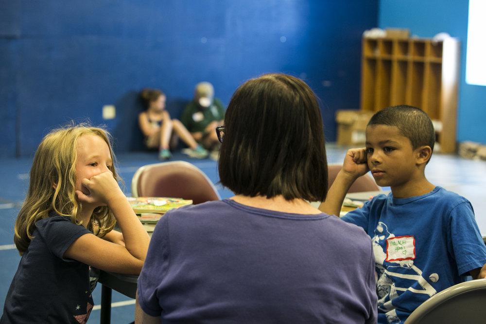Brianne Burdick and Malachi Easley listen to volunteer Dawn Halvorsen while she reads books.