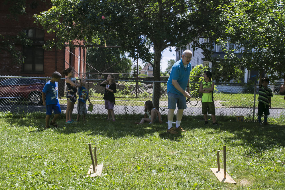 Volunteer Richard Waigand shows children from first through third grades how to play ring toss.