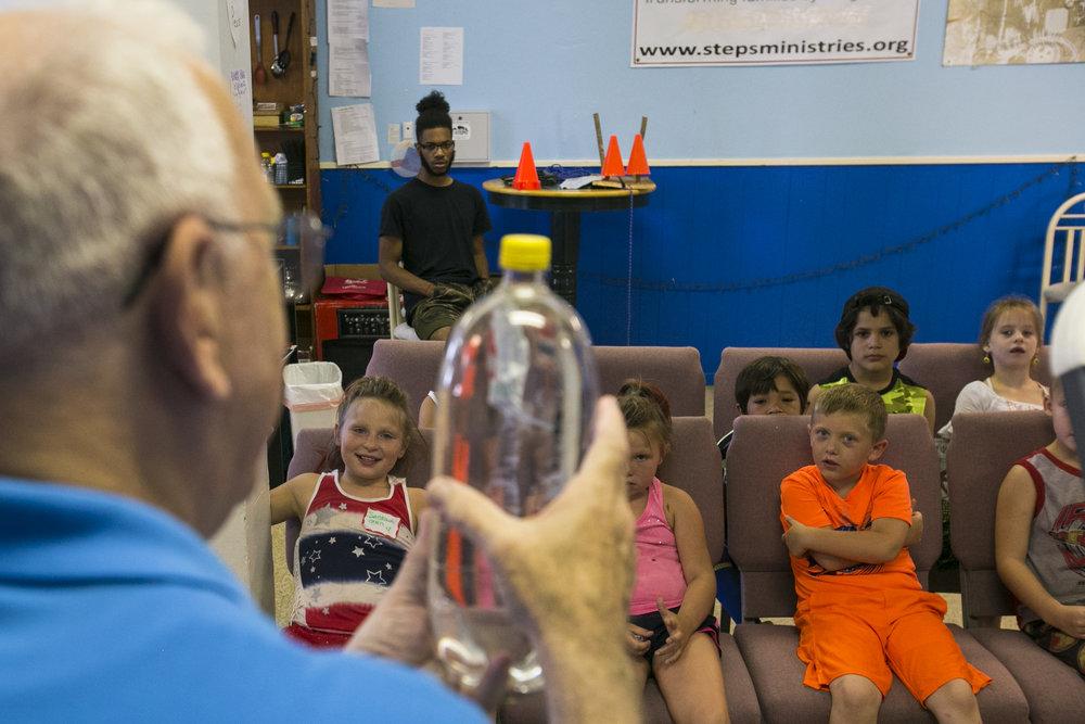 Volunteer Richard Waigand shows children how boats flow on water.