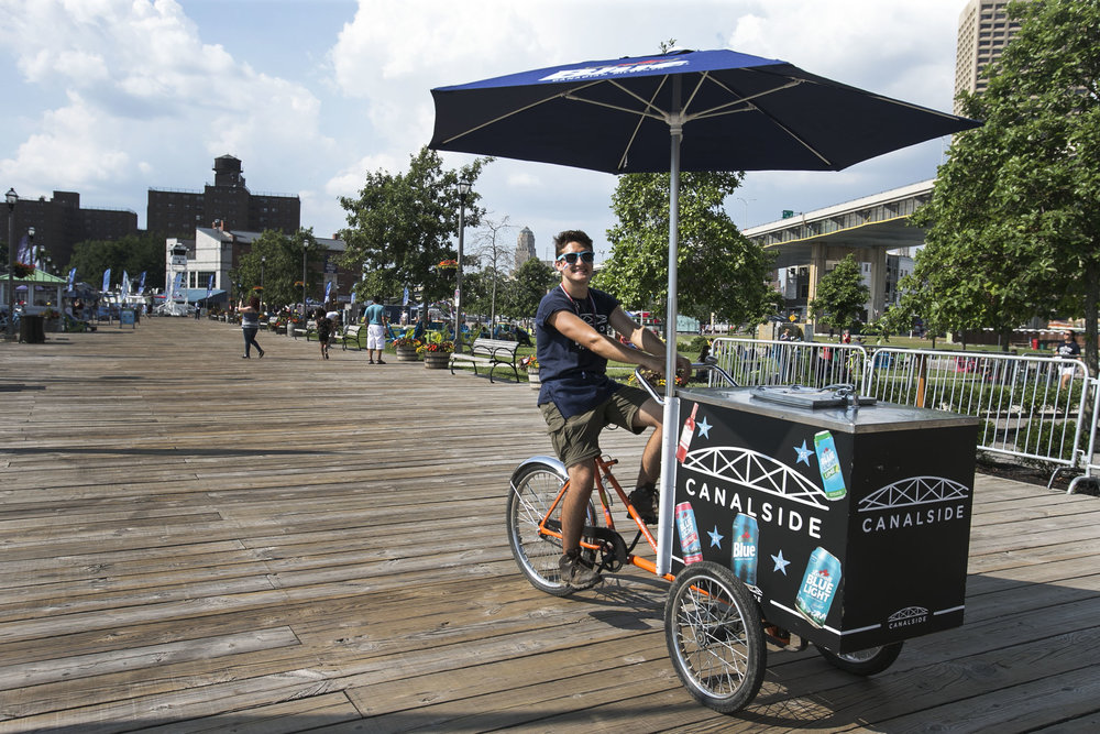 Operations staff Girard Mariotto rides a bar cart.