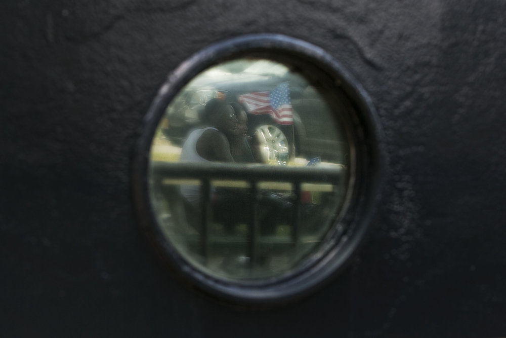 The reflection of Carnell Gwynn and Sasha Caldwell sitting together with a flag on the table is showed on the ship's body.