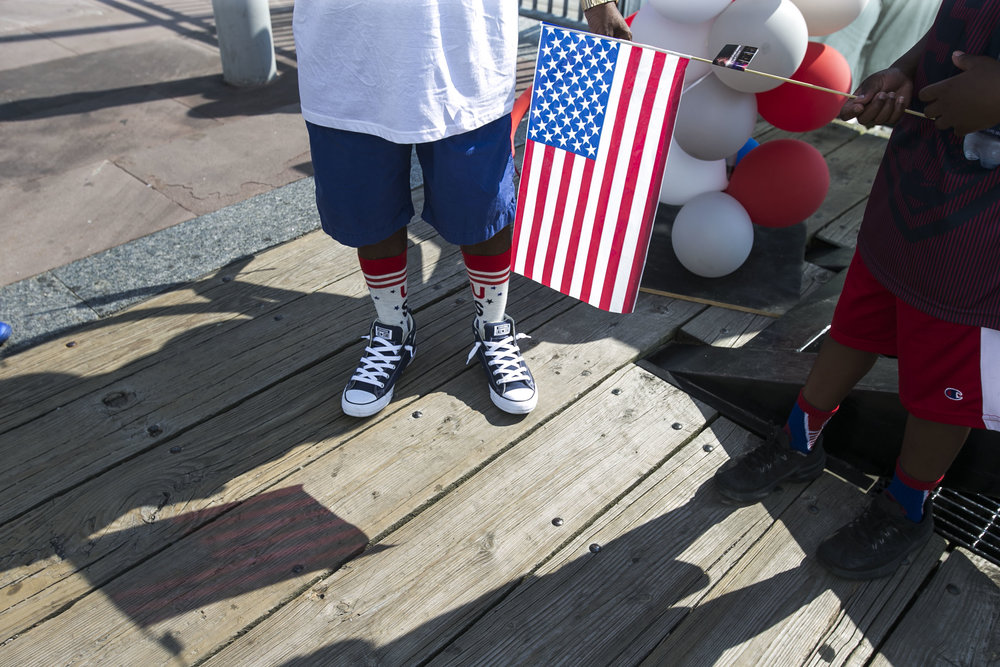 Jabari Reed, 9, holds a flag that is reflected on the wood planks.