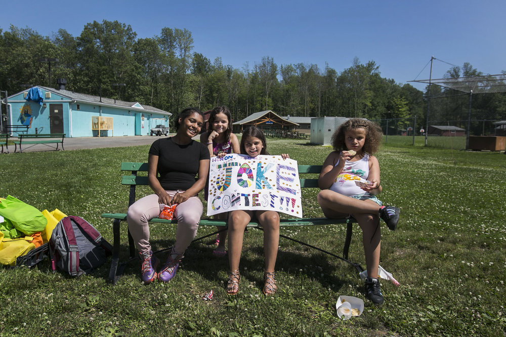 Shaina Slusser, 9, Falastine Fadel, 9, Alexa Frazier, 8, and their counselor Nadeau Jenkins, exhibit a sign they draw.