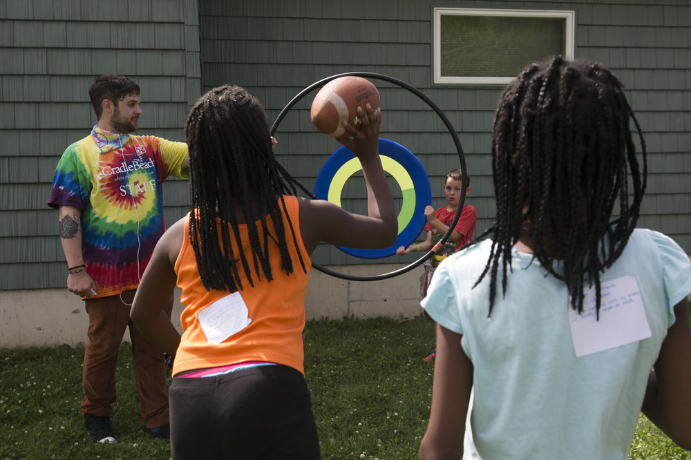 Syria Nelson, 10, tosses a football to Damon Quick, while counselor James Calabrese holds a hula hoop.