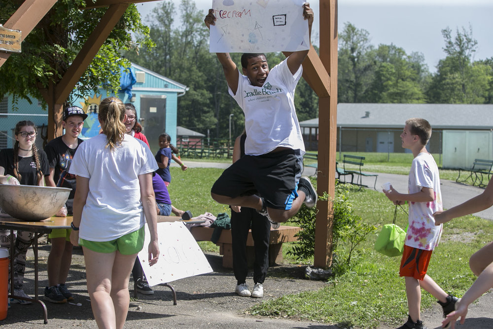 Jeremiah Lewis, a 16-year-old pioneer camper, holds a sign for ice cream.