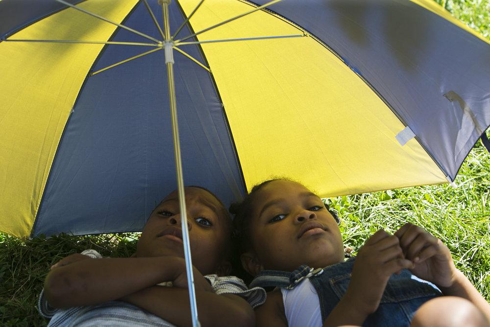 Caleb Fisher, 6, and Olivia Ellison, 7, lie under an umbrella.
