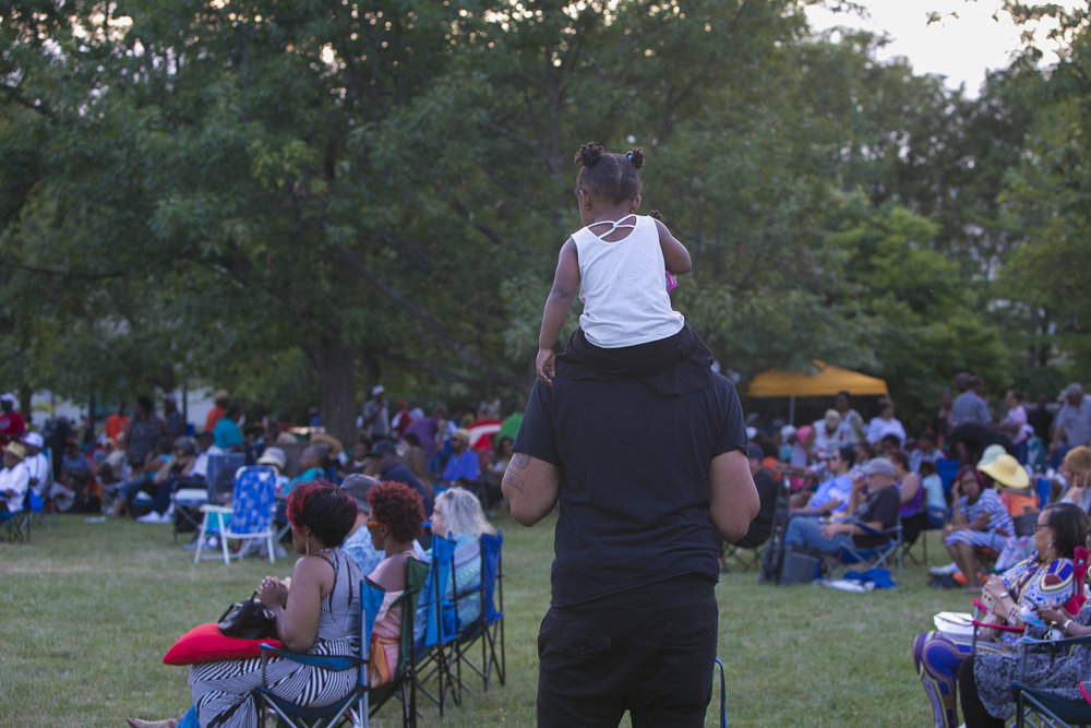 Keiliani Overton, 2, rides on shoulders to get a better view.