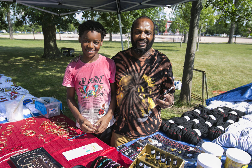 Elijah Mack II and his 11-year-old godson, Camarion Dixon, sell shirts and jewelry at the festival.