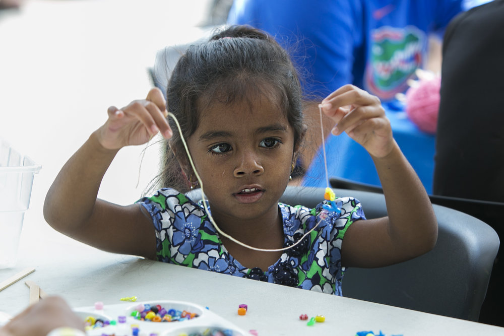 Adwita Swami, 4, makes a necklace for herself.