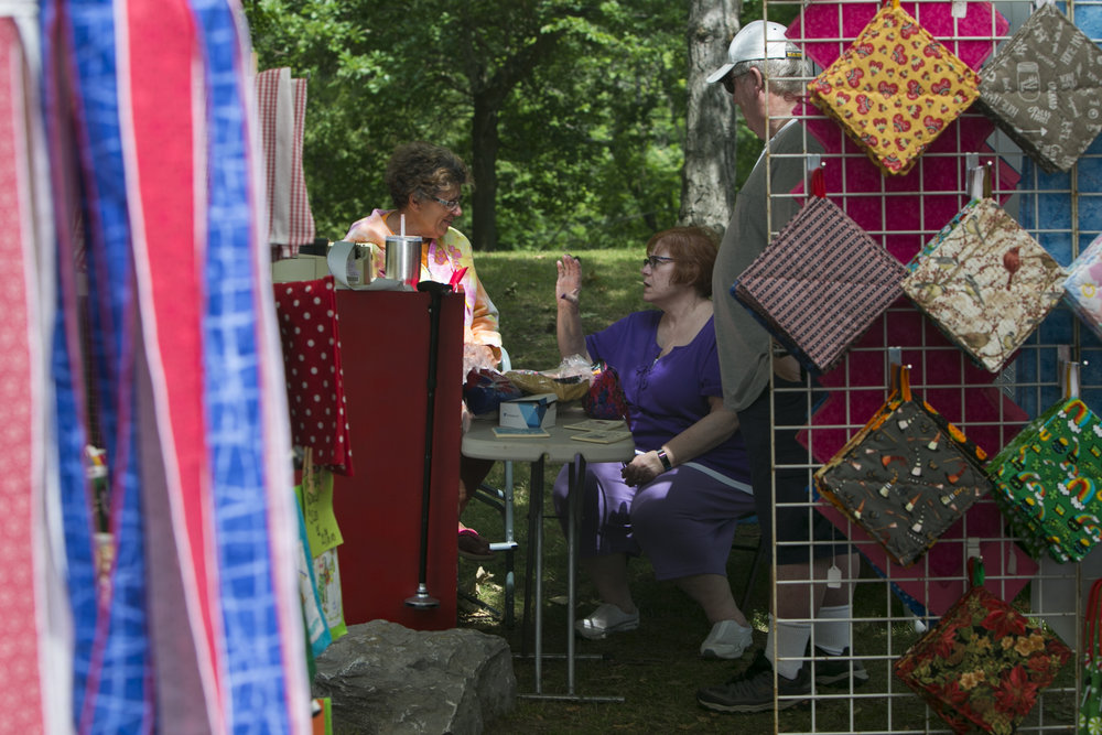 Nicki Nuwer, owner of Crafts by Nicki, displays and sells her handmade home decorations at the festival. She chats with her friend Jane Hammann from Lancaster, New York.