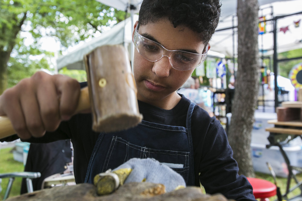 Shayden Hudson, 14, resizes a spoon ring using a hammer.