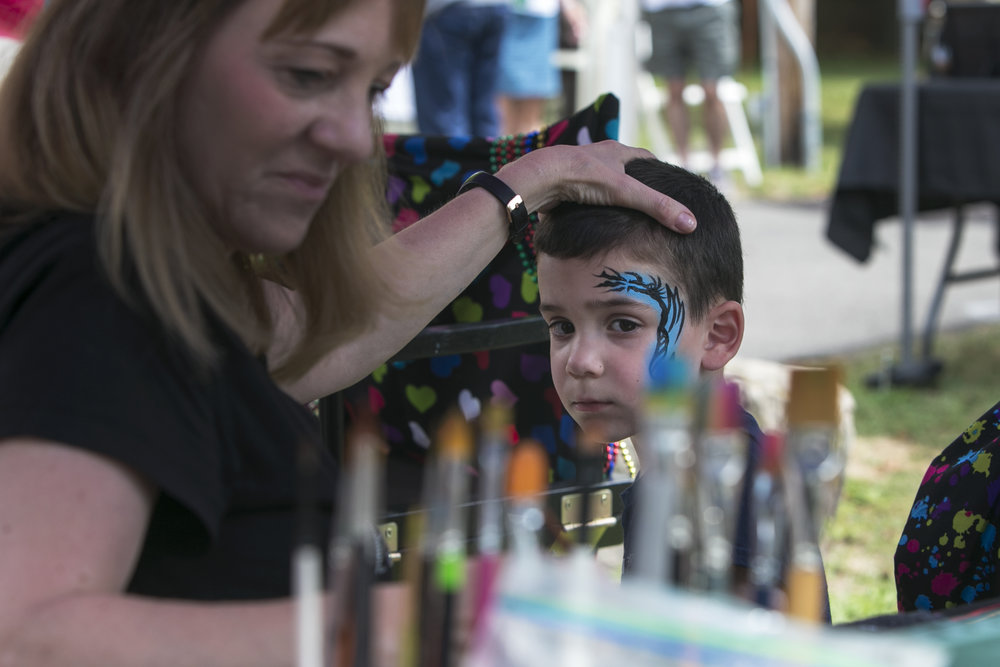 Dominic Polino, 3, gets his face painted by Linda Gawron.