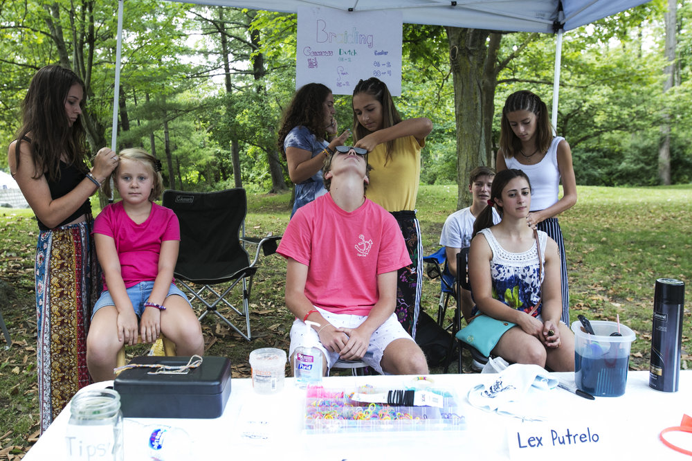 Lex Putrelo, Lena Galante, and Clara Richards, all from Williamsville South High School, provide hair braiding at the festival.