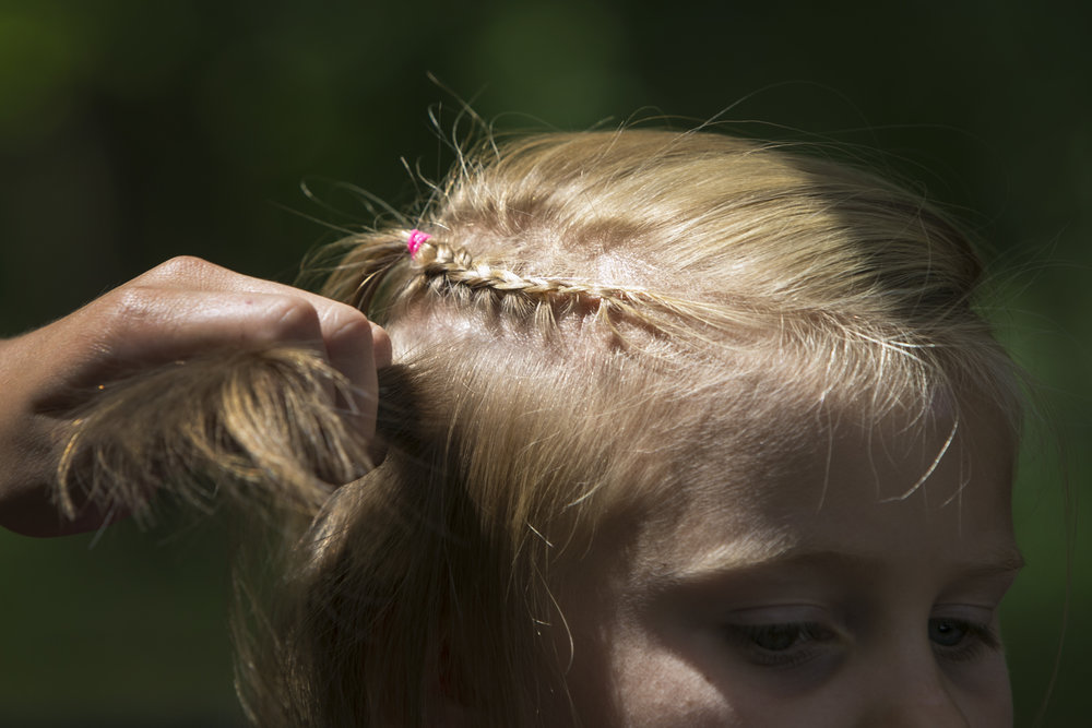 Zoe Bryce, 8, gets her hair braided.