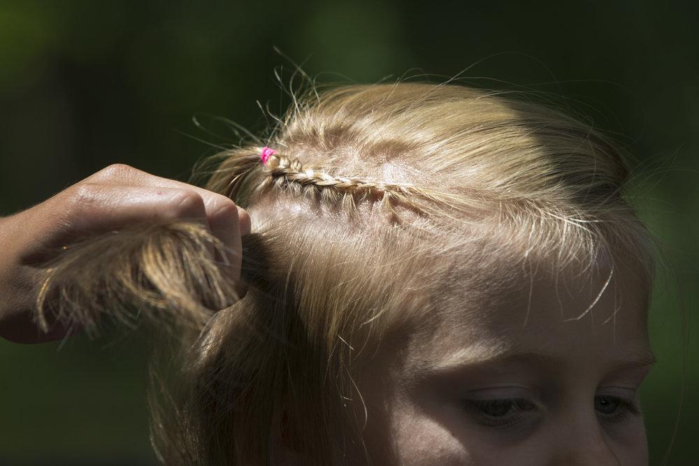 Zoe Bryce, 8, gets her hair braided.