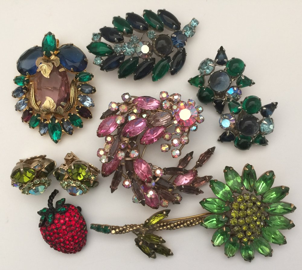 At the top is a beautiful unsigned jeweled pin that is from the 1960s. The blue and green leaf and matching earrings are Weiss from the late 1950s. I bought the large pink jeweled pin in the mid 1960s to wear on a pink satin formal dress that I made to wear to a special banquet with my future husband. I wore the beautiful Weiss green flower pin and the unsigned earrings with a green silk dress. The little Weiss strawberry is from the early 1960s and has always been a favorite of mine that I still wear.