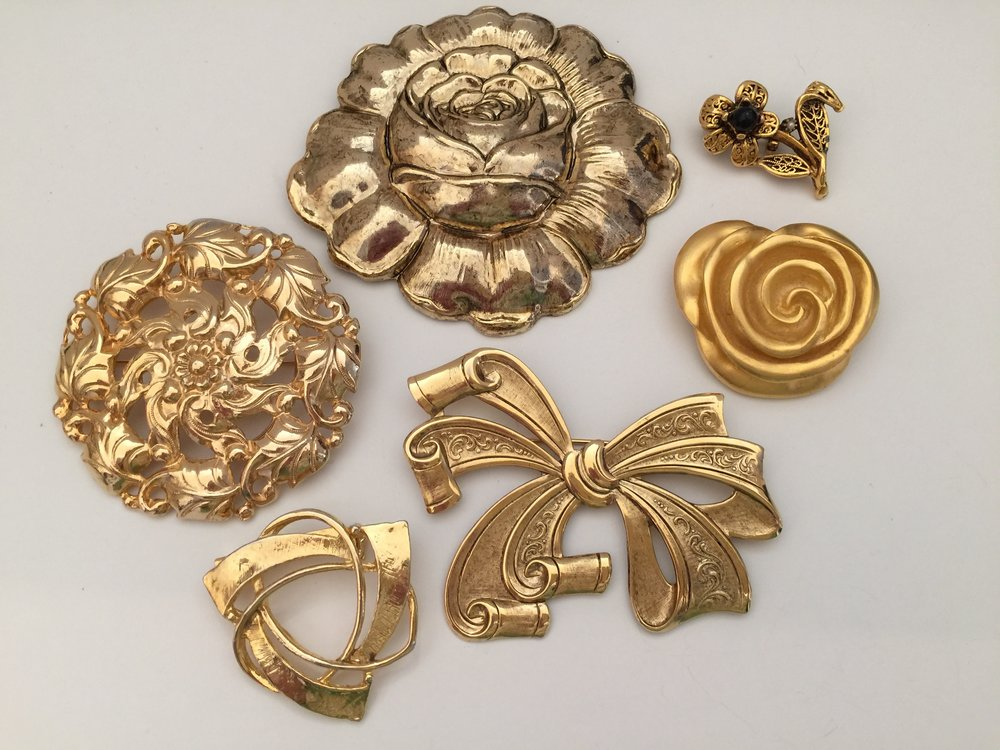 Some of my gold pins ... the large round pin on the left if a Dauplaise brand pin.  The other pins are unsigned.   My sister gave me the small flower.