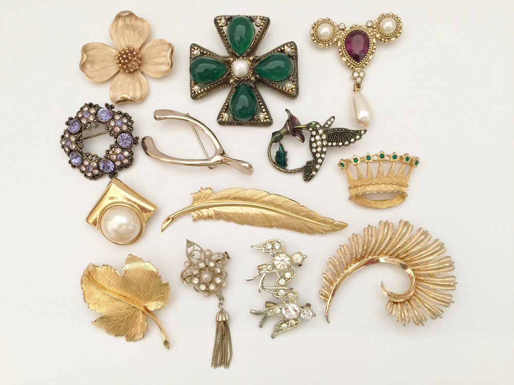 I inherited these pins from my mother. The large dogwood blossom and the small gold with pearl pins are Trifari. The humming bird and the two purple jeweled pins are the 1928 brand. The long gold feather is Monet. The small crown with green stones is a VAN S Authentics from the 1960s. The large gold curved feather is Coro. The other pins are unsigned. I always loved the small gold pearl and tassel pin; it was one of my mother's favorites and dates from the 1950s or possibly earlier.