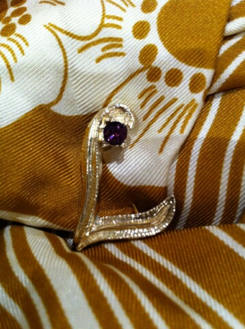 My mother's little initial pin with amethyst stone ... currently pinned to the coat on one of my daughters.