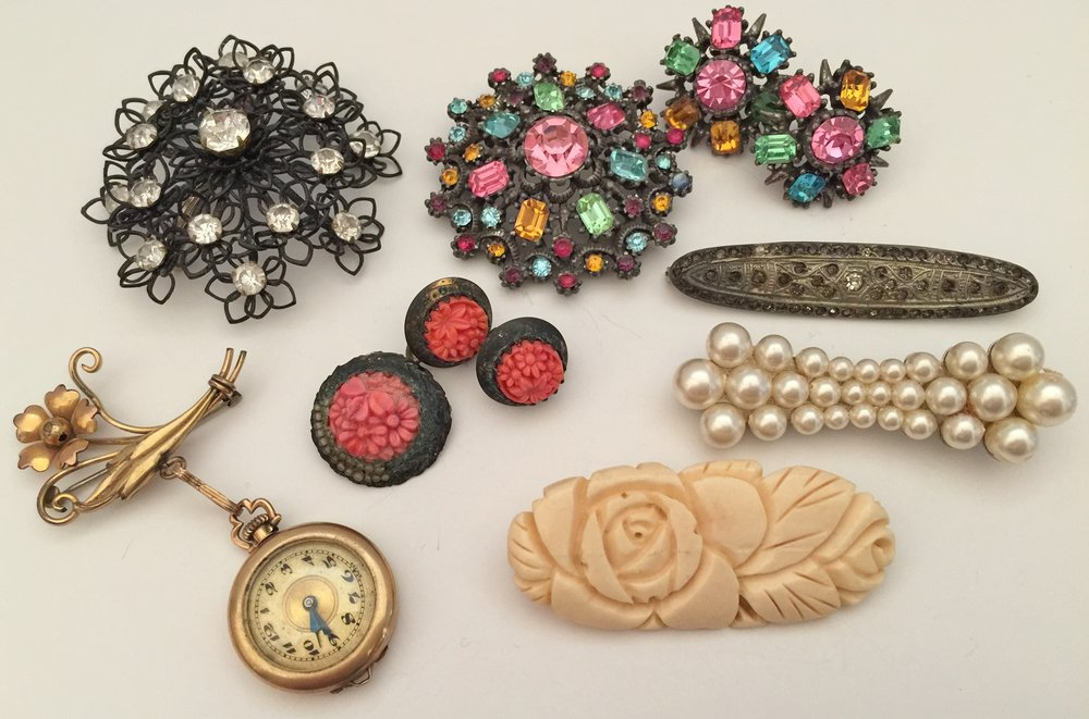 Beautiful antique pins that belonged to my grandmother... 1881-1957. Large Black wire and rhinestone pin is not signed. The jeweled brooch and matching earrings are Coro ... probably the 1940s. The small silver marcasite collar pin has unfortunately lost most of it's stones which are actually small pieces of pyrite set in silver. The pearl collar pin is still lovely and desirable. Below is a Bakelite pin. The little gold watch belonged to my aunt who died in 1937 ... her name is engraved on the back. The watch pin is a Carl Art pin that dates from the 1930's. The tiny orange pin is no more than an inch in diameter, probably Bakelite. I chanced to find the matching earrings at an antique mall!