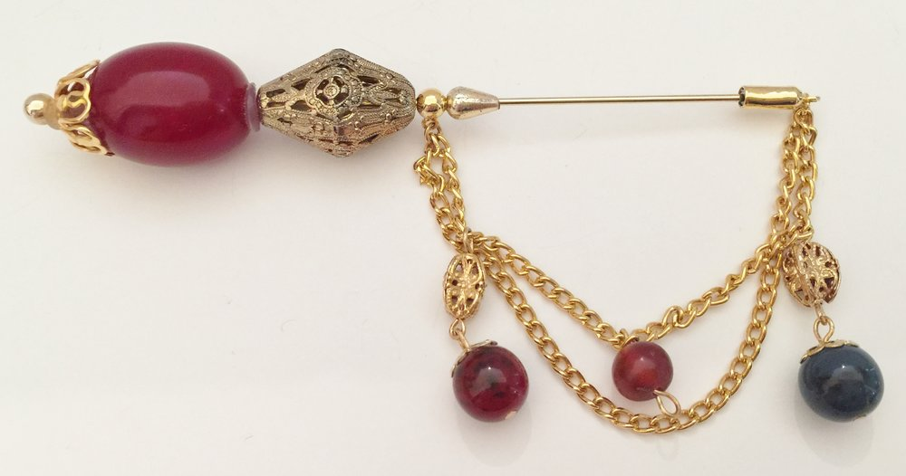 A very large stick pin that is impressive on a coat or jacket.