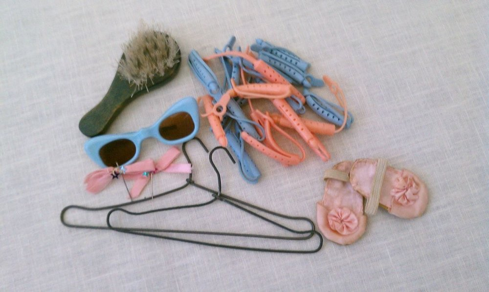 Hair brush and rubber curlers ... two small hangers ... tiny blue sunglasses. My mother made the tiny hair bows to wear with the pink satin gown and the tiny pink slippers were made to wear with the pink print night gown.