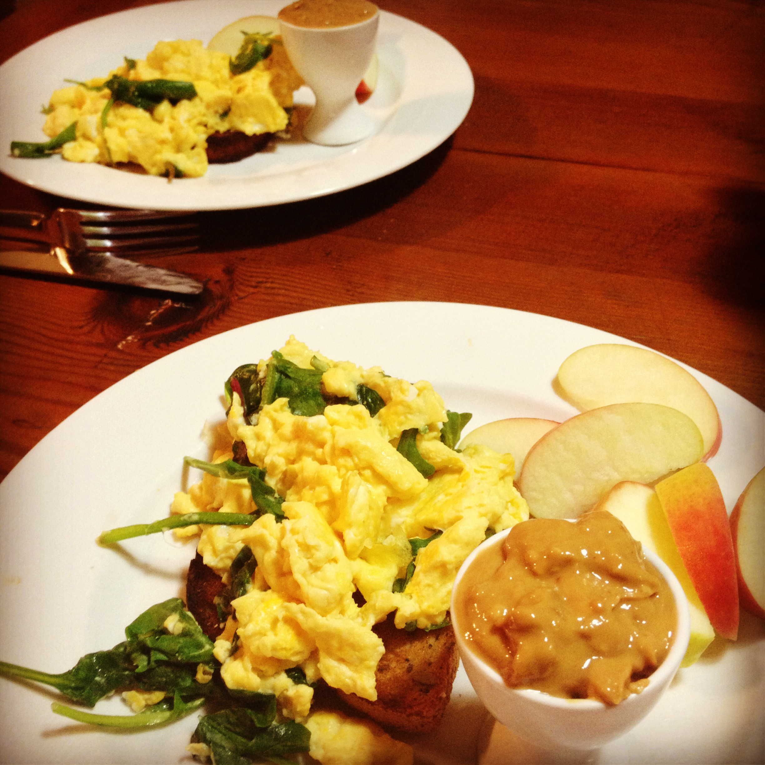 Scrambled eggs with spinach, and a side of apple and peanut butter.