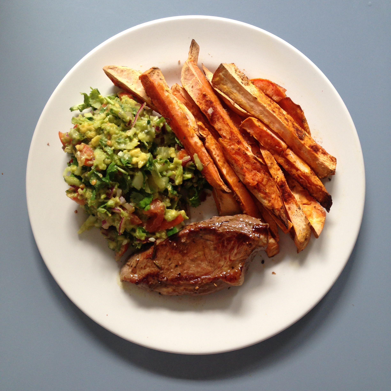 A lazy Paleo meal: free-range steak, sweet potato fries and guac/salsa combo.