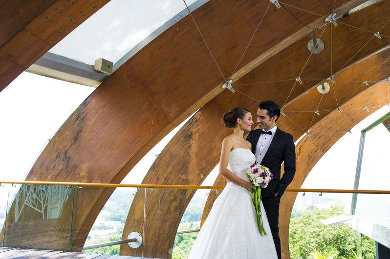 Newly Weds Under Wooden Archs - One Faber Group
